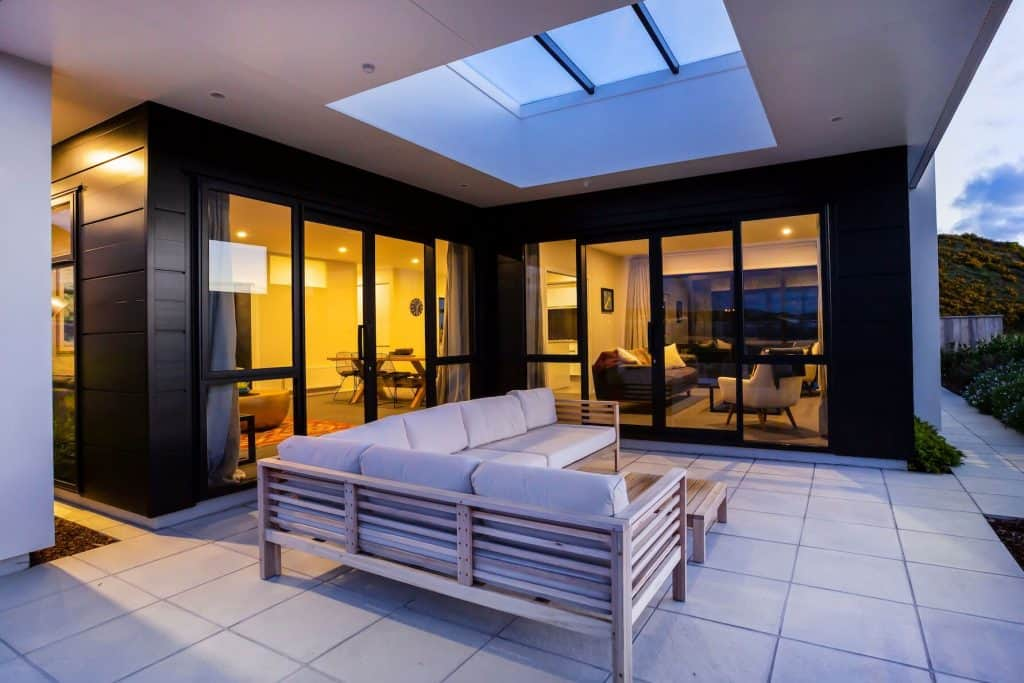 New Home Aotea - Indoor/outdoor, Black window joinery. Skylights, Exterior paving.