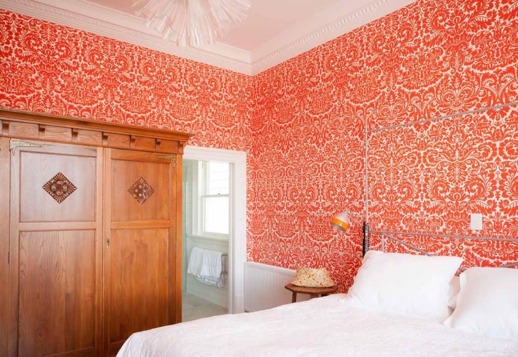 Mt Victoria villa - Orange flocked wallpaper., Orange and white bedroom.